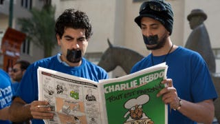 Protestors in Tel Aviv, Israel, hold a copy of the latest issue of French satirical magazine Charlie Hebdo during a demonstration Feb. 5, 2015, calling on Israeli authorities to allow the sale of the controversial magazine in the country. MENAHEM KAHANA/Getty Images