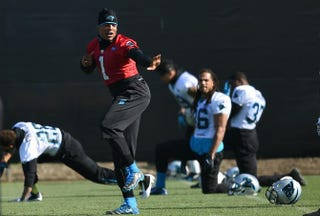 Quarterback Cam Newton of the Carolina Panthers gives the Heisman Trophy pose while his teammates stretch during practice at San Jose State University on Feb. 5, 2016, California.Thearon W. Henderson/Getty Images