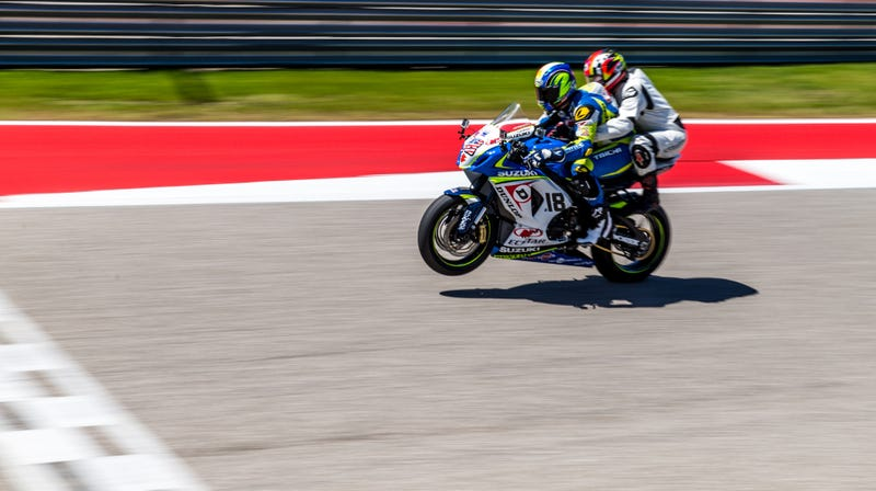 Me, on the back of a very fast MotoAmerica Superbike, trying not to focus on the fact that two people were balancing on one wheel at this point in time. Photo credit: Kurt Bradley