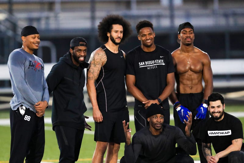 Colin Kaepernick, center, stands with Bruce Ellington, Brice Butler, Jordan Veasy, and Ari Werts during the Colin Kaepernick NFL workout held at Charles R. Drew High School on Nov. 16, 2019, in Riverdale, Ga.