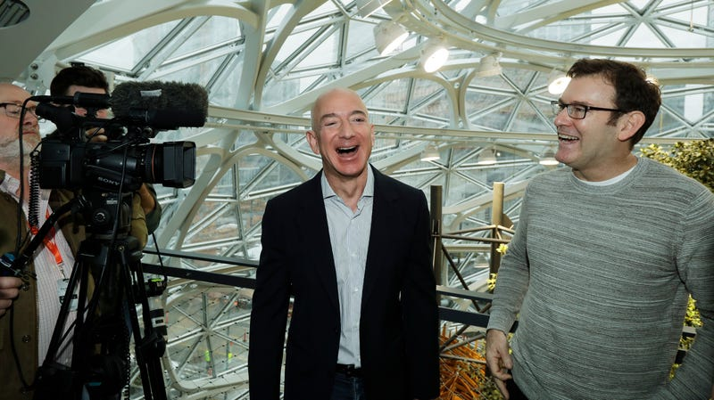 Jeff Bezos, center, the CEO and founder of Amazon.com, laughs as he talks with Ron Gagliardo, right, the lead horticulturist of the Amazon Spheres, following the grand opening ceremony for the plant-filled geodesic domes built for Amazon.com employees.