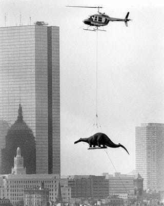 Illustration for article titled A Curious Photo of a Dinosaur being Airlifted over Boston
