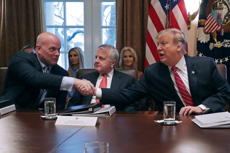 President Donald Trump, right, reaches over Deputy Secretary of State John Sullivan to shake hands with acting Attorney General Matthew Whitaker during a meeting of Trump's cabinet in the Cabinet Room at the White House February 12, 2019 in Washington, DC. Trump said he was not happy about the compromise legislation agreed to by Republicans and Democrats that would prevent a new partial federal government shutdown but said he would accept the deal.