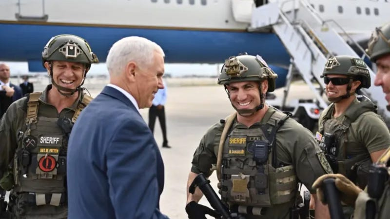 Illustration for article titled Mike Pence Tweets and Later Deletes Photo With Florida Sheriff's Deputy Sporting a QAnon Patch