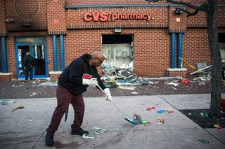 Jerald Miller helps clean up debris April 28, 2015, from a CVS pharmacy in Baltimore that was set on fire during rioting after the funeral of Freddie Gray.Andrew Burton/Getty Images