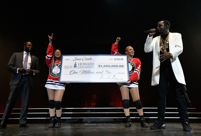 """Sean """"Diddy"""" Combs (right) presents Howard University President Wayne A.I. Frederick with $1 million check at the Puff Daddy and Bad Boy Family Reunion Tour at the Verizon Center on Sept. 22, 2016, in Washington, D.C.Larry French/Getty Images for Live Nation"""