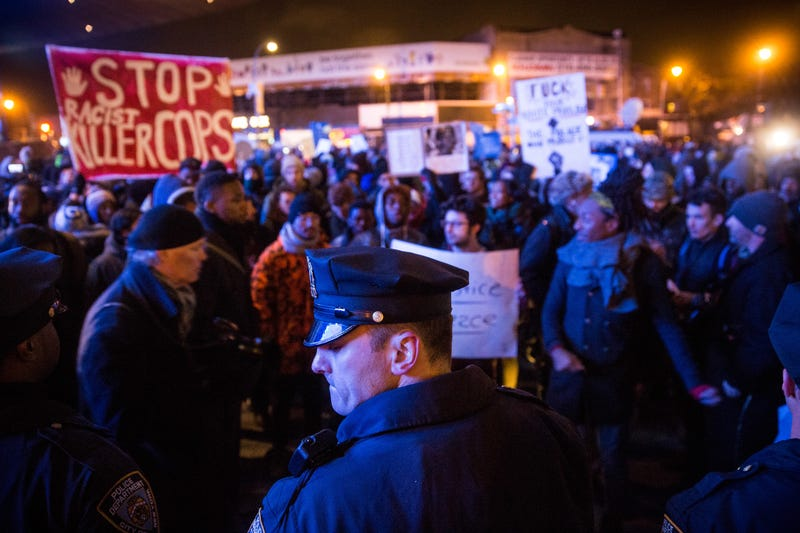 Police officers protect people entering the Barclays Center for a Brooklyn Nets game while demonstrators protest a Staten Island, New York grand jury's decision not to indict a police officer involved in the chokehold death of Eric Garner in July on December 8, 2014 in New York City.
