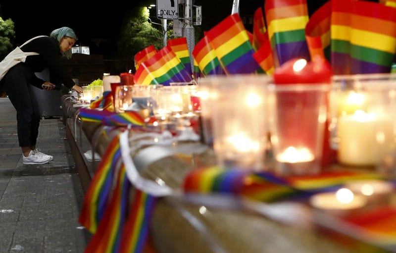 A woman lights a candle during a candlelight vigil for the victims of the Pulse Nightclub shooting in Orlando, Florida, on June 13, 2016, in Sydney, Australia. Daniel Munoz/Getty Images