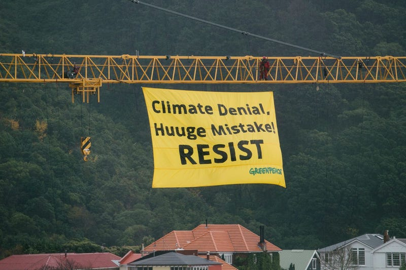Two environmental activists scale a crane in Wellington and unfurl a banner to welcome Secretary of State Rex Tillerson in New Zealand (Photo courtesy of the New Zealand Green Party)