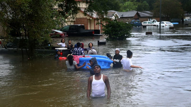 People walk down a street flooded by Harvey as they evacuate their homes in Houston.