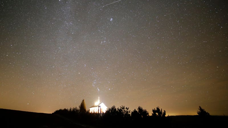 A meteor streaks across the sky during the annual Geminids meteor shower over an Orthodox church. Image via AP.