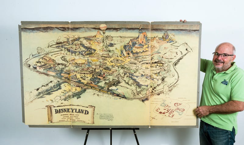 Art dealer Mike Van Eaton stands next to an original hand-drawn map of Disneyland from 1953. Image: AP
