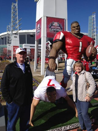 Illustration for article titled Colin Kaepernick's Parents Posed In Front Of A Statue Depicting The Atlanta Falcons Giving Their Son A Wedgie