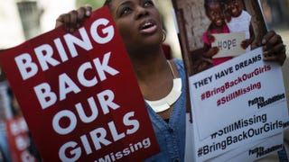 A woman holds a sign as other protesters gather outside the Nigeria House in London April 14, 2015, to mark the one-year anniversary since a group of Nigerian schoolgirls were abducted in Nigeria.Dan Kitwood/Getty Images