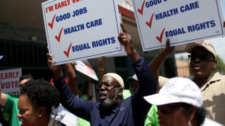 Voters hold up signs as they walk to an early-voting site to cast their primary-election ballots on Aug. 11, 2014, in Miami.Joe Raedle/Getty Images