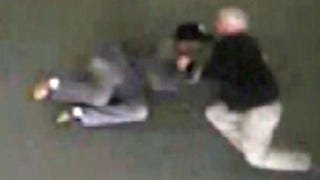 Michael Foster (right) in video footage showing him tackling and restraining Clarence Daniels for carrying a firearm—that was legally registered. Foster was arrested and charged with battery.YouTube