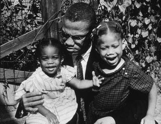 Malcolm X sits with daughters in 1963 (Getty)