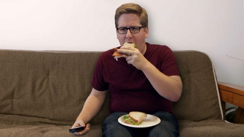 Illustration for article titled Man Concerned He Spread Himself Too Thin Between Eating Sandwich, Watching Television