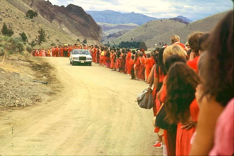 La salida de Rajneesh en unos de sus coches de lujo es recibida por una fila de Rajneeshees. Wikimedia Commons