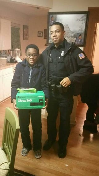 The unidentified 11-year-old poses with his brand-new Xbox and games and a Memphis police officer.Memphis Police Department via Facebook