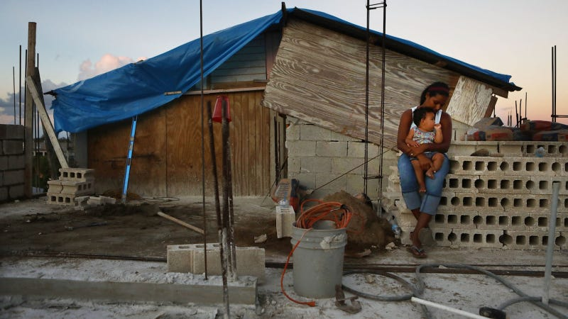 Mother Isamar holds her baby Saniel, 9 months, at their makeshift home, under reconstruction, after being mostly destroyed by Hurricane Maria, on December 23, 2017 in San Isidro, Puerto Rico.