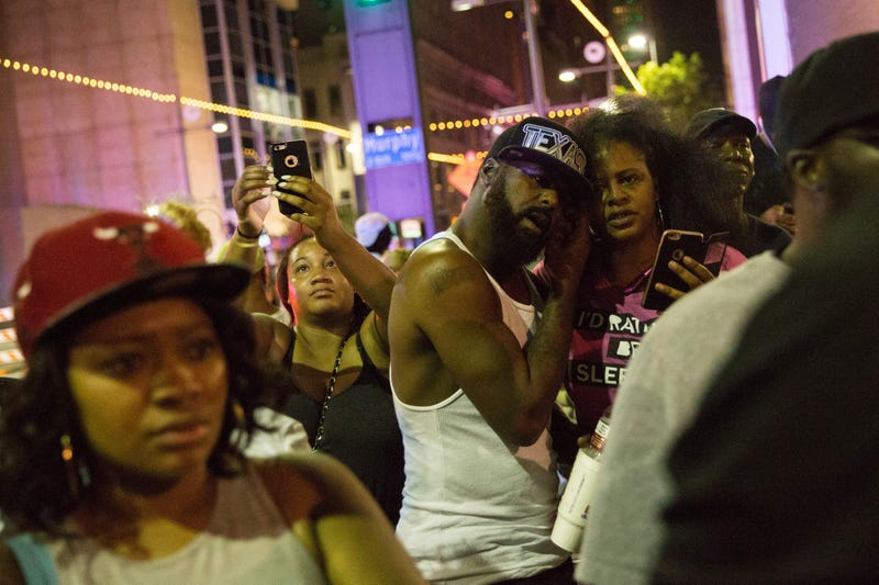 Protesters yell after police officers arrest a bystander following a shooting after what had been a peaceful protest in Dallas on July 7, 2016, over police brutality. At least five police officers were killed in the Dallas shooting following the protest.  Two suspected snipers were in custody by early morning July 8, 2016, authorities said.LAURA BUCKMAN/AFP/Getty Images