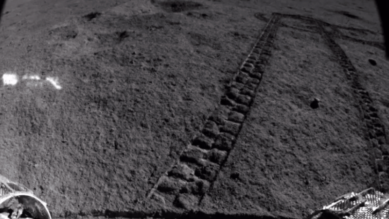 The Yutu 2 rover looking back on its progress, with two of its wheels visible in the bottom corners.