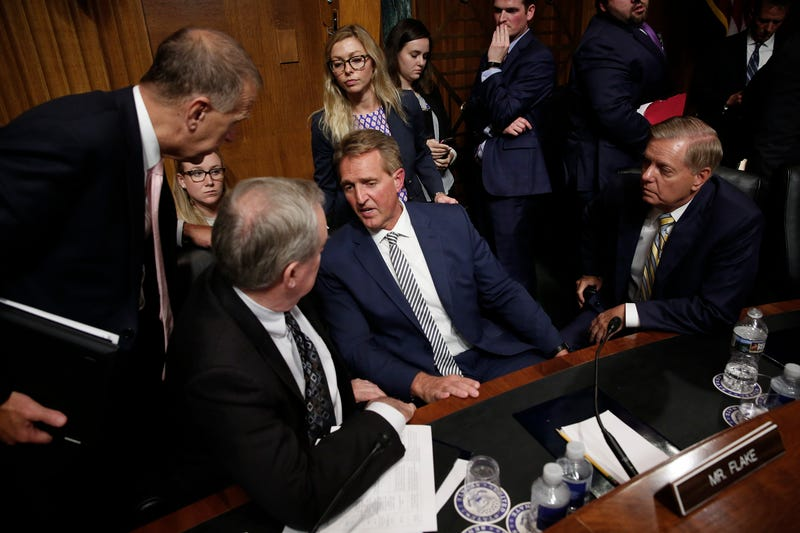 Republican members of the Senate Judiciary Committee surround Sen. Jeff Flake (C) (R-AZ) after he announced he was in favor of a delay in the Kavanaugh nomination process during a committee meeting in the Dirksen Senate Office Building on Capitol Hill September 28, 2018 in Washington, DC.