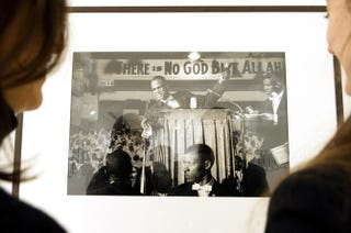 Two people at the Arts Sensus Gallery in London on March 1, 2012, pose next to a picture showing Malcolm X giving a speech at a black Muslim rally in Washington, D.C., in 1961, photographed by U.S. photojournalist Eve Arnold.MIGUEL MEDINA/AFP/Getty Images
