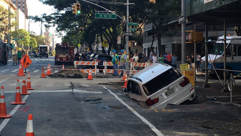 Water main break floods streets, sends SUV into sinkhole