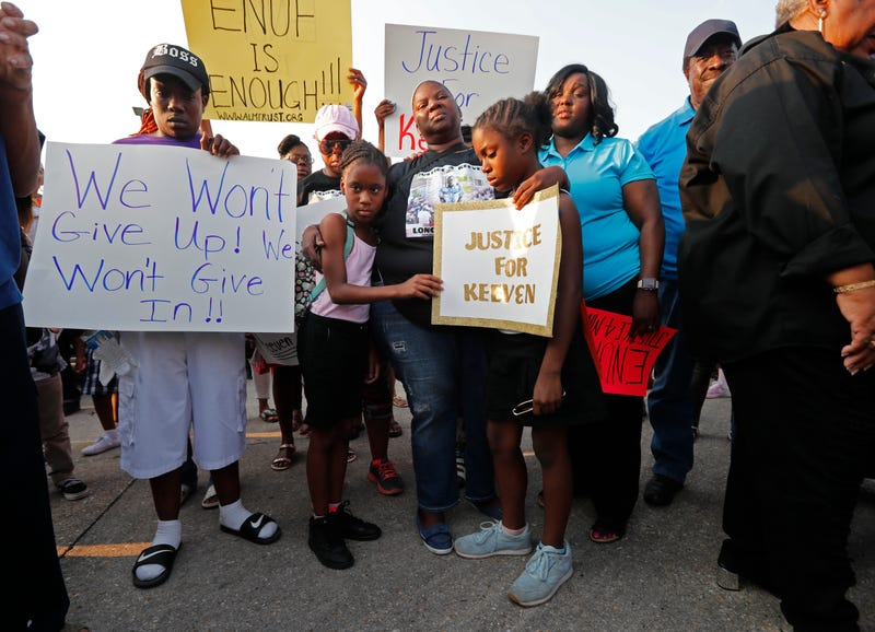 Kiwanda Robinson (center), mother of Keeven Robinson, holds family friends Madysen Johnson (right) and Madysen's sister Morgan Johnson at the start of a solidarity march for Keeven in Jefferson Parish, La., on May 14, 2018.