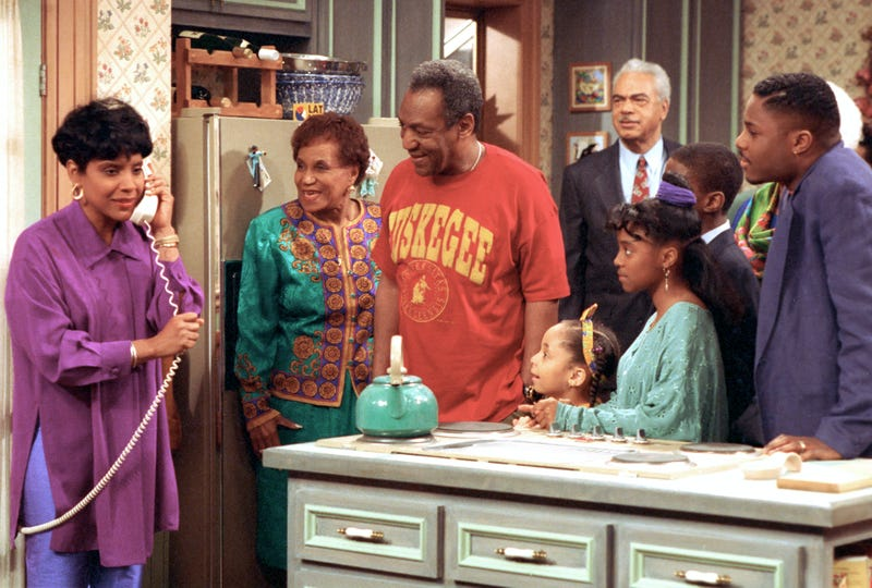 Phylicia Rashad as Clair Huxtable talks on the telephone while Bill Cosby, as Dr. Cliff Huxtable, and other cast members of The Cosby Show gather around during taping of the final episode in New York City on March 6, 1992.