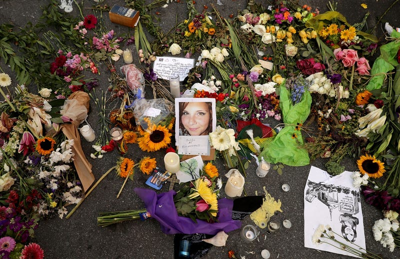 Flowers, candles and chalk-written messages surround a photograph of Heather Heyer on the spot where she was killed and 19 others injured when a car slammed into a crowd of people protesting a white supremacist rally Aug. 16, 2017, in Charlottesville, Va.  (Chip Somodevilla/Getty Images)