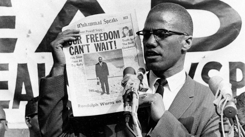 Malcolm X holds up a paper for the crowd to see during a Black Muslim rally in New York City on Aug. 6, 1963.