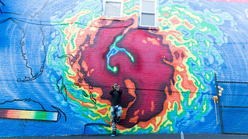 Mathematics, the creator of the iconic Wu-Tang Clan logo, stands before the mural.
