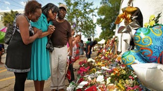 Mourners pray together in front of the historic Emanuel African Methodist Church on June 20, 2015, in Charleston, S.C., where nine people were shot to death.Chip Somodevilla/Getty Images