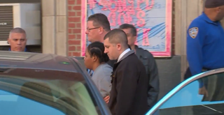 Tenisha Fearon is escorted by officers after she allegedly tossed her 6-month-old daughter from the sixth-floor window of her Bronx, N.Y., apartment.ABC 7 New York Screenshot
