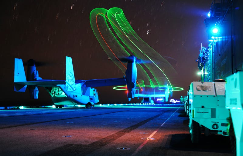 Illustration for article titled An MV-22 Osprey Fills The Night Sky Over The USS Boxer With Psychedelic Slinkies