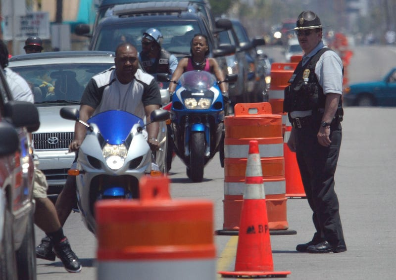 "Motorcyclists ride down Ocean Boulevard in Myrtle Beach, S.C., under the watchful eye of a local law enforcement officer on May 27, 2005, during ""Black Bike Week."""