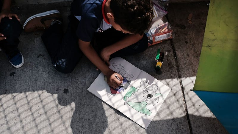 A Honduran child works in a coloring book while waiting with his family along the border bridge after being denied entry from Mexico into the U.S. on June 25, 2018 in Brownsville, Texas.