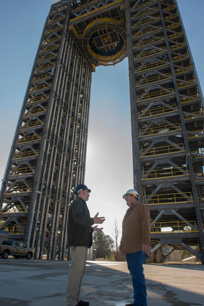 NASA engineers Robert Bobo (left) and Mike Nichols (right) talk beneath the 221-foot-tall Test Stand 4693. (Image: NASA/MSFC/Emmett Given)
