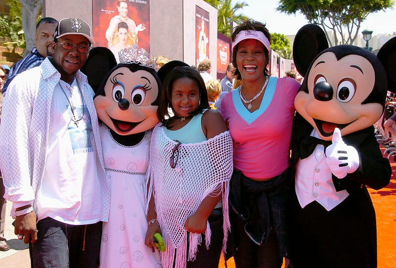 Bobby Brown and Whitney Houston with their daughter, Bobbi Kristina (Lisa Rose/Disney Parks via Getty Images)