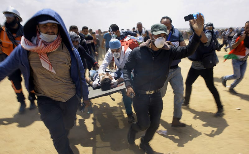 Palestinian medics and protesters evacuate a seriously wounded youth during a deadly protest at the Gaza Strip's border with Israel, east of Khan Younis, Gaza Strip, on May 14, 2018. Thousands of Palestinians are protesting near Gaza's border with Israel as Israel celebrates the inauguration of a new U.S. Embassy in contested Jerusalem.