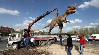 Illustration for article titled What's Better Than A Giant Gundam Statue? A Dinosaur, Apparently.