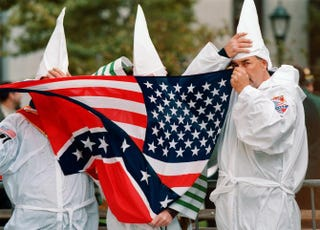 Three members of the Ku Klux Klan hide behind a combination of Confederate and American flags in New York Oct. 23, 1999.DOUG KANTER/AFP/Getty Images