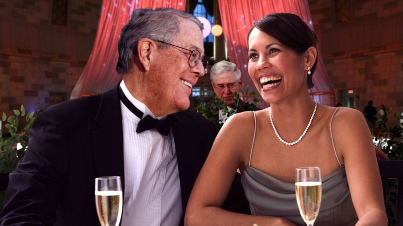David Koch charms a beautiful socialite with flirtatious banter, while brother Charles awaits his cue to step in and astound her with his knowledge of free enterprise.