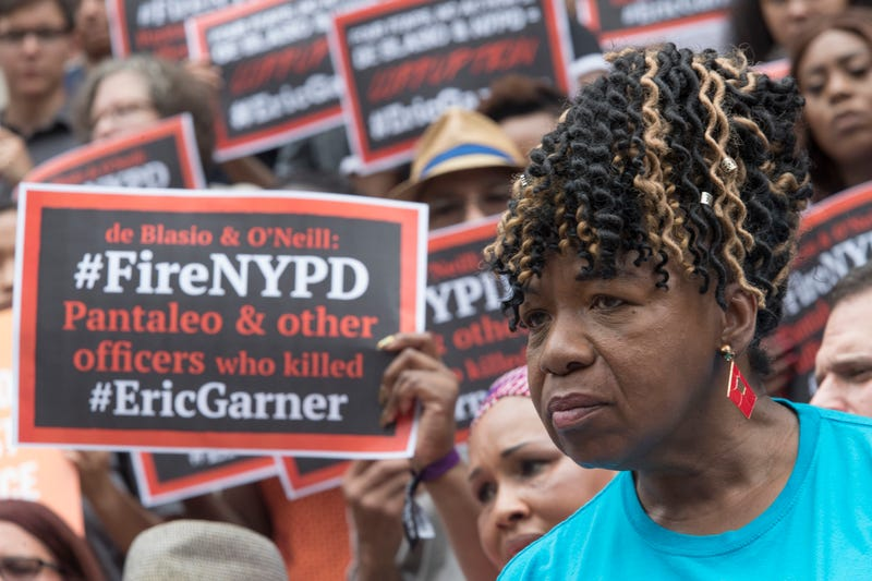 Gwen Carr, whose son Eric Garner was killed by an NYPD officer, surrounded by supporters at City Hall.