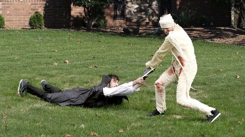 A mummy and a vampire fighting over a sneaker.