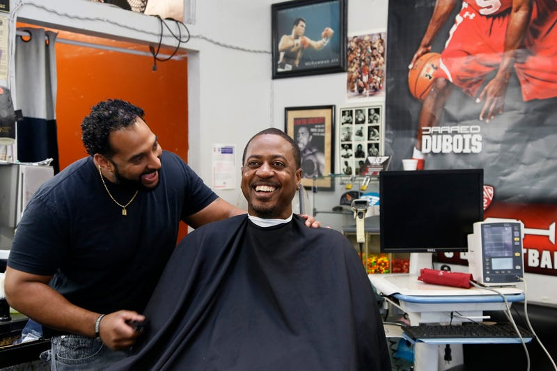 Barber Eric Muhammad, owner of A New You Barbershop, jokes with regular customer Marc M. Sims before measuring his blood pressure in Inglewood, Calif., on March 11, 2018.