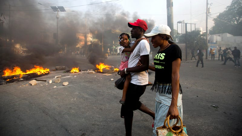 People walk past a barricade during a protest over the cost of fuel in Port-au-Prince, Haiti, Friday, July 6, 2018.
